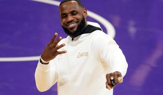 Los Angeles Lakers forward LeBron James reacts after receiving his NBA championship ring before an NBA basketball game against the Los Angeles Clippers, Tuesday, Dec. 22, 2020, in Los Angeles. (AP Photo/Marcio Jose Sanchez)