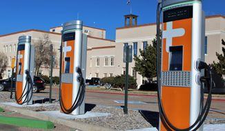 This Dec. 21, 2020 image provided by the New Mexico General Services Department shows some of the recently installed electric vehicle charging stations at the Bataan Memorial Building in Santa Fe, New Mexico. State officials said the stations can be used by both government and private vehicles. (Thom Cole/New Mexico General Services Department, via AP)