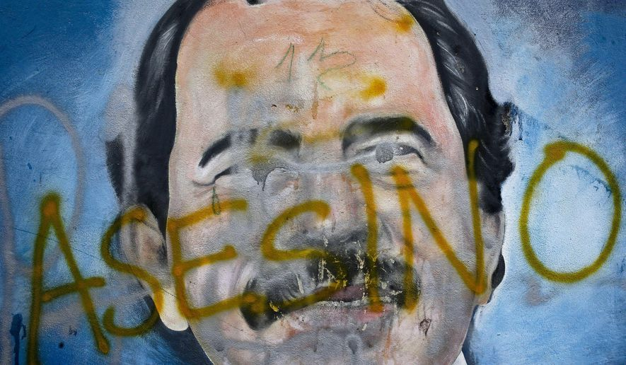 """FILE - In this May 26, 2018 file photo, the Spanish word for """"Murderer"""" covers a mural of Nicaragua's President Daniel Ortega, as part of anti-government protests demanding his resignation in Managua, Nicaragua. Nicaragua's ruling party-dominated Congress has passed a law Monday, Dec. 21, 2020, that would essentially ban opposition candidates from running in the 2021 presidential elections, giving President Daniel Ortega the power to unilaterally declare citizens """"terrorists"""" or coup-mongers, classify them as """"traitors to the homeland"""" and ban them from running as candidates. (AP Photo/Esteban Felix, File)"""