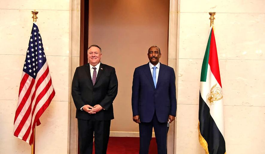 FILE - In this Aug. 25, 2020 file photo, U.S. Secretary of State Mike Pompeo stands with Sudanese Gen. Abdel-Fattah Burhan, the head of the ruling sovereign council, in Khartoum, Sudan.  On Tuesday, Dec. 22, 2020, Sudan's Justice Ministry said the U.S. Congress has moved forward on Washington's promise to end the African country's pariah status. The ministry said that Congress passed legislation that restored to Sudan what is known as sovereign immunity, a measure that would effectively stop future compensation claims from being filed against it in U.S. courts. (Sudanese Cabinet via AP, File)