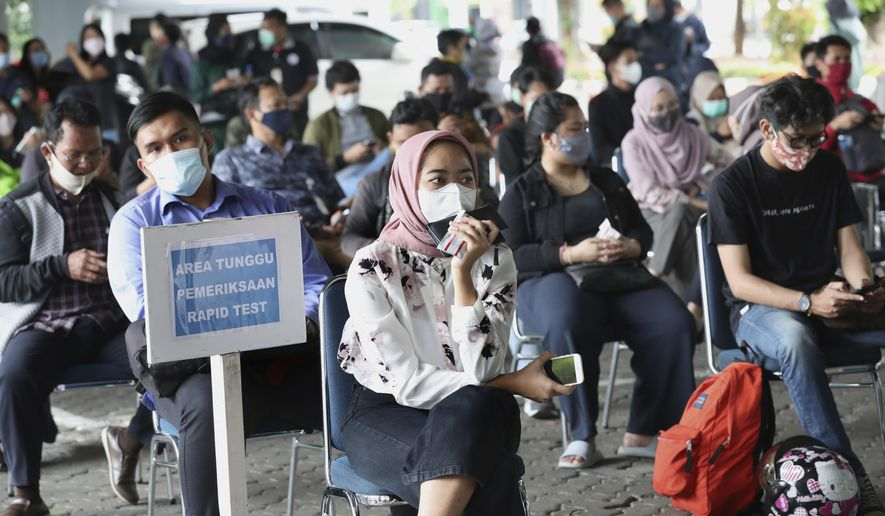 Passengers sit apart to maintain physical distance as they wait to have their nasal swab samples collected to be tested for the coronavirus which is required for long-distance train trips at Gambir Train Station in Jakarta, Indonesia, Tuesday, Dec. 22, 2020. Indonesia has reported more than 600,000 cases of the coronavirus. (AP Photo/Tatan Syuflana)