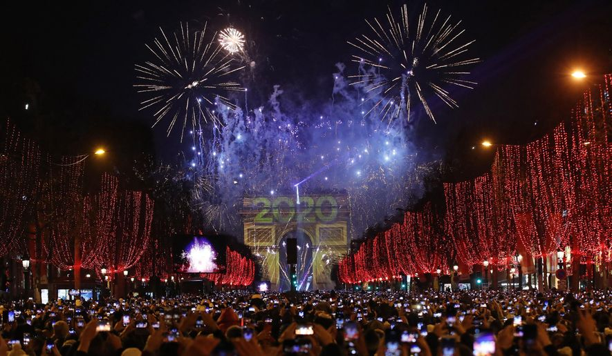 Revellers photograph fireworks over the Arc de Triomphe as they celebrate the New Year on the Champs Elysees, in Paris, France, Wednesday, Jan. 1, 2020. Few years in Europe's postwar history will be so little missed as 2020. It kicked open the door to fear, upheaval and death on a scale unrivalled in peacetime for more than a century. Death walked unabashed in cities and villages, the lonely rooms of retirement homes, the overwhelmed intensive care units of hospitals. (AP Photo/Christophe Ena)