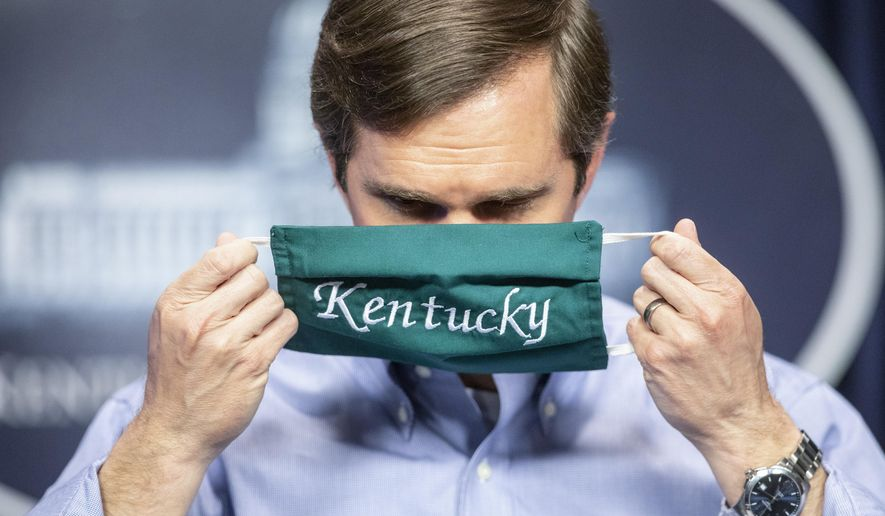 FILE - In this May 11, 2020, file photo, Kentucky Gov. Andy Beshear puts on a face mask after speaking to reporters at the Capitol in Frankfort, Ky. (Ryan C. Hermens/Lexington Herald-Leader via AP, File)