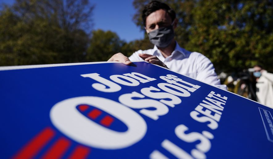FILE-In this Wednesday, Nov. 18, 2020 file photo, Georgia Democratic candidate for U.S. Senate Jon Ossoff grabs signs to give out during a drive-thru yard sign pick-up event on, in Marietta, Ga.  For the second time in three years, Jon Ossoff is campaigning in overtime. The question is whether the 33-year-old Democrat can deliver a win in a crucial Jan. 5 runoff with Republican Sen. David Perdue.  (AP Photo/Brynn Anderson, File)