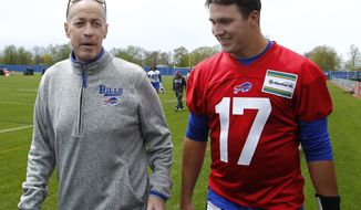 """FILE - In this May 11, 2018, file photo, Buffalo Bills rookie quarterback Josh Allen (17) walks with Hall of Fame quarterback Jim Kelly following the team's NFL football rookie minicamp in Orchard Park, N.Y. Kelly has made a point of keeping his distance by limiting his chats with Allen via text for much of this year. Kelly's decision has less to do with the coronavirus pandemic as it does Kelly not wanting to distract the third-year starter. """"He doesn't need me in his ear, so I pretty much leave him alone,"""" Kelly told The Associated Press. (AP Photo/Jeffrey T. Barnes, File)"""