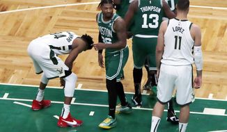 Milwaukee Bucks' Giannis Antetokounmpo (34) reacts beside Boston Celtics' Marcus Smart (36) after missing his second free throw after being fouled with less than a second left on the clock during the second half of an NBA basketball game, Wednesday, Dec. 23, 2020, in Boston. (AP Photo/Michael Dwyer)