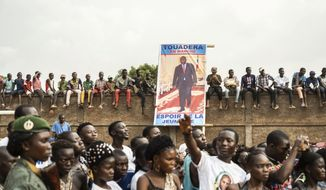 In this photo released by Xinhua News Agency, supporters gather near the poster of Faustin-Archange Touadera, President of the Central African Republic, as they take part in a campaign rally in Bangui, Central African Republic, Dec. 12, 2020. China evacuated more than 200 nationals to a safer area after eight Chinese mining company vehicles were stolen during armed conflict ahead of an election in the Central African Republic, its embassy said Wednesday, Dec. 23, 2020. (André Bâ/Xinhua via AP)