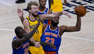 Indiana Pacers forward Domantas Sabonis (11) passes between New York Knicks center Mitchell Robinson (23) and forward Julius Randle (30) during the first half of an NBA basketball game in Indianapolis, Wednesday, Dec. 23, 2020. (AP Photo/Michael Conroy)