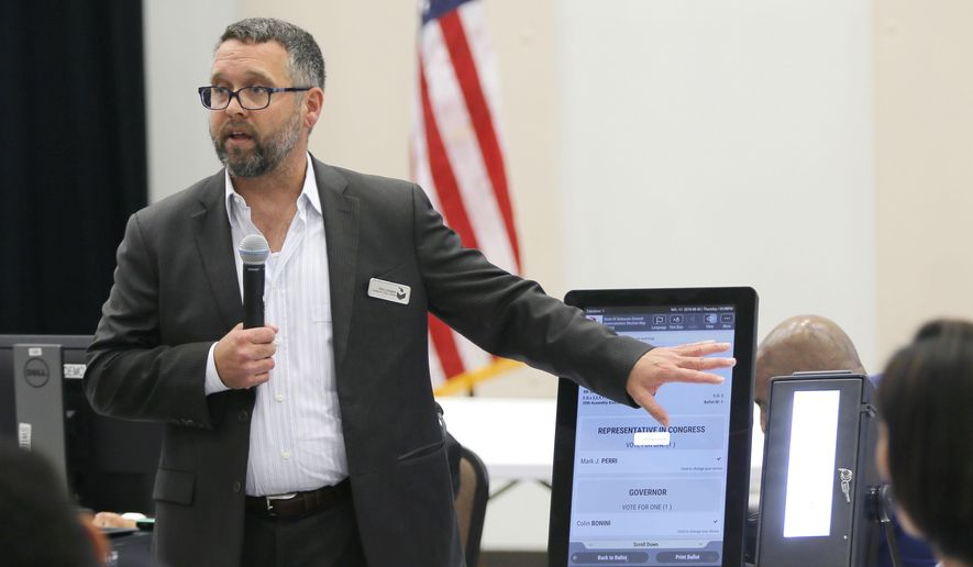 Eric Coomer from Dominion Voting demonstrates his company's touch screen tablet. Eric Coomer, driven into hiding by death threats has filed a defamation lawsuit against President Donald Trump's campaign, two of its lawyers and some conservative media figures and outlets, Tuesday, Dec. 22, 2020. (Bob Andres/Atlanta Journal-Constitution via AP, File)