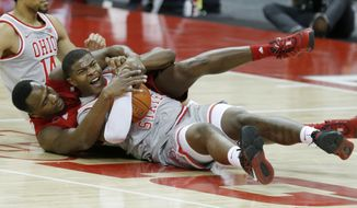 Rutgers forward Mamadou Doucoure, left, works for a loose ball against Ohio State forward E.J. Liddell during the first half of an NCAA college basketball game in Columbus, Ohio, Wednesday, Dec. 23, 2020. (AP Photo/Paul Vernon)