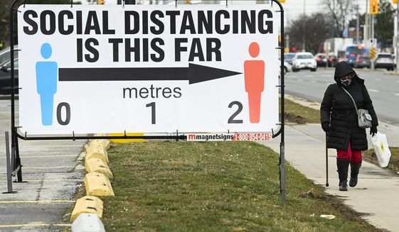 A person walks past a COVID-19 restrictions sign during the COVID-19 pandemic in Mississauga, Ontario, on Tuesday, Dec. 22, 2020. (Nathan Denette/The Canadian Press via AP)