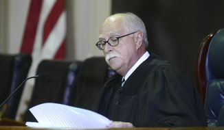 In this 2016 photo, Muskingum County Common Pleas Judge Mark C. Fleegle reads during a court proceeding in Zanesville, Ohio. In December 2020, Fleegle, who failed to adopt written rules for mask wearing and other coronavirus prevention measures, has been barred from overseeing two upcoming trials. His lack of written procedures makes it difficult for jurors and others to know what's expected of them, Ohio Supreme Court Chief Justice Maureen O'Connor said in an order. (Chris Crook/Times Recorder via AP)