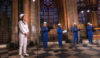 In this photo provided by Maitrise Notre-Dame de Paris soprani singer Julie Fuchs and the Notre Dame Cathedral choir recording a Christmas concert on Saturday, Dec. 19, 2020, inside Notre Dame Cathedral in Paris. The concert will be broadcasted on French television on Christmas. (MSNDP/Musique Sacree à Notre-Dame de Paris via AP)