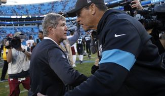 FILE - In this Dec. 1, 2019, file photo, Washington Redskins coach Bill Callahan and Carolina Panthers coach Ron Rivera speak following an NFL football game in Charlotte, N.C. Washington coach Rivera's first game against his old team could also be a chance for his new team to clinch the NFC East title. Washington would wrap up the NFL's weakest division by beating the Panthers if the New York Giants lose to Baltimore. It'll unquestionably be an emotional day for Rivera with a playoff berth potentially at stake against the team he led for the previous nine seasons. (AP Photo/Brian Blanco, File)