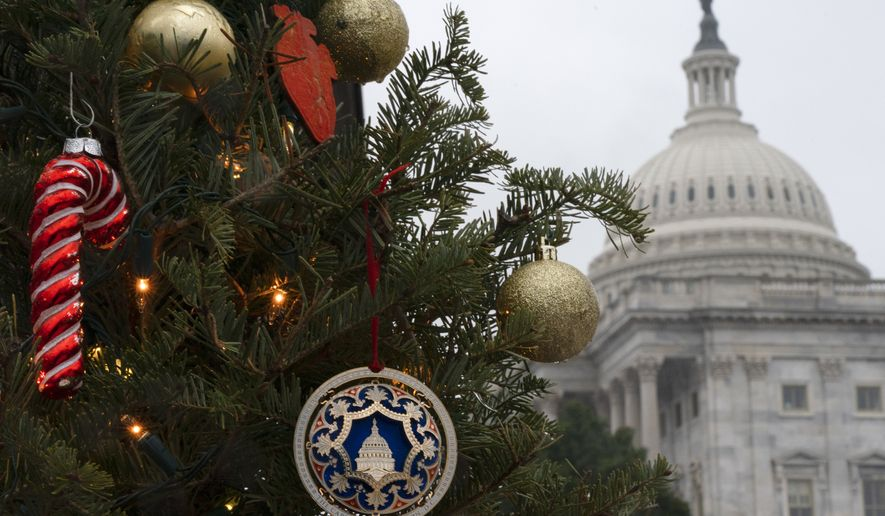 A small tree has been decorated for the Christmas holiday, with the U.S. Capitol seen behind it, Thursday, Dec. 24, 2020, in Washington. (AP Photo/Jacquelyn Martin)