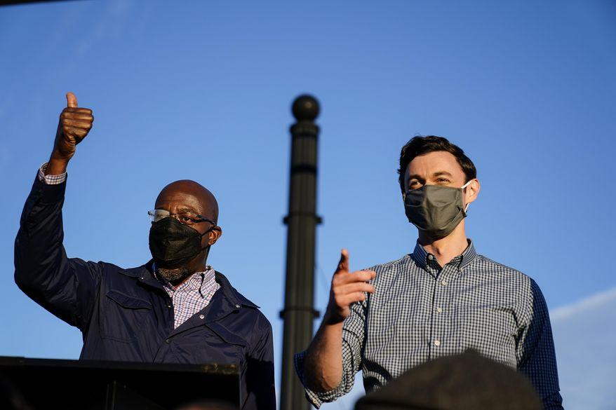 Georgia Democratic candidates for U.S. Senate Raphael Warnock (left) and Jon Ossoff gesture toward a crowd during a campaign rally on Sunday, Nov. 15, 2020, in Marietta, Ga. (AP Photo/Brynn Anderson) **FILE**