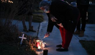 A neighbor lights a candle at a small memorial near the site of the fatal police shooting of Andre Hill on Wednesday, Dec. 23, 2020 on Oberlin Drive in Columbus, Ohio. Hill, 47, was shot and killed by Columbus Division of Police officer Adam Coy after responding to a suspicious vehicle call around 1:30 a.m., on Tuesday, Dec. 22, 2020 in the 1000 block of Oberlin Drive. Body camera footage released Wednesday shows Andre Hill, a 47-year-old Black man, emerging from a garage and holding up a cellphone in his left hand seconds before he is fatally shot by a Columbus police officer. (Joshua A. Bickel/The Columbus Dispatch via AP)