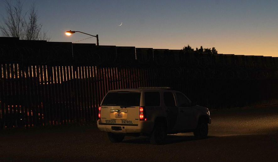 A U.S. Border Patrol vehicle sits parked near where a Las Posadas event at the U.S.-Mexico border wall took place, as several asylum seeking families participate in the event on the Mexico side of the border fence Tuesday, Dec. 15, 2020, in Douglas, Ariz. (AP Photo/Ross D. Franklin)