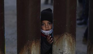 A young boy, part of several asylum seeking families participating in a Las Posadas event at the U.S.-Mexico border wall, peers into the U.S. from Agua Prieta, Mexico Tuesday, Dec. 15, 2020, seen from Douglas, Ariz. People on each side of the border celebrate Las Posadas as they have done for decades, a centuries-old tradition practiced in Mexico re-enacts Mary and Joseph's search for refuge in Bethlehem through songs, with several of the families attending stuck south of the border, their lives in limbo with U.S. proceedings suspended amid the COVID-19 pandemic. (AP Photo/Ross D. Franklin)