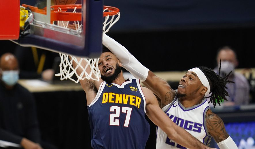Denver Nuggets guard Jamal Murray, left, is hit by Sacramento Kings center Richaun Holmes while driving to the rim in the first half of an NBA basketball game Wednesday, Dec. 23, 2020, in Denver. (AP Photo/David Zalubowski)
