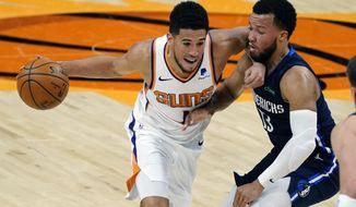 Phoenix Suns guard Devin Booker (1) drives on Dallas Mavericks guard Jalen Brunson during the second half of an NBA basketball game Wednesday, Dec. 23, 2020, in Phoenix. (AP Photo/Rick Scuteri)