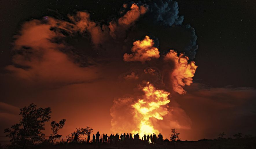 In this photo provided by the National Park Service, people watch an eruption from Hawaii's Kilauea volcano on the Big Island on Sunday, Dec. 20, 2020. The volcano shot steam and an ash cloud into the atmosphere which lasted about an hour, an official with the National Weather Service said early Monday, Dec. 21, 2020. (Janice Wei/National Park Service via AP)