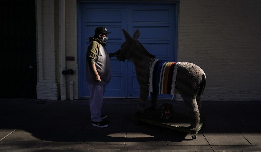Jesus Hernandez, a merchant who owns a gift shop on Olvera Street that only opens on weekends due to the coronavirus pandemic, waits for a key to store his uncle's life-size stuffed donkey, a photo prop named George, in downtown Los Angeles, Wednesday, Dec. 16, 2020. Olvera Street, known as the birthplace of Los Angeles, has been particularly hard hit by the pandemic, with shops and restaurants closed and others barely hanging on. (AP Photo/Jae C. Hong) ** FILE **