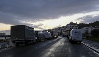 General view of the queue of trucks in the area outside the Port of Dover waiting for a ferry as police block the entrance to the Port of Dover, in Dover, England, Wednesday, Dec. 23, 2020. Freight from Britain and passengers with a negative coronavirus test have begun arriving on French shores, after France relaxed a two-day blockade over a new virus variant. The blockade had isolated Britain, stranded thousands of drivers and raised fears of shortages. (AP Photo/Alberto Pezzali)