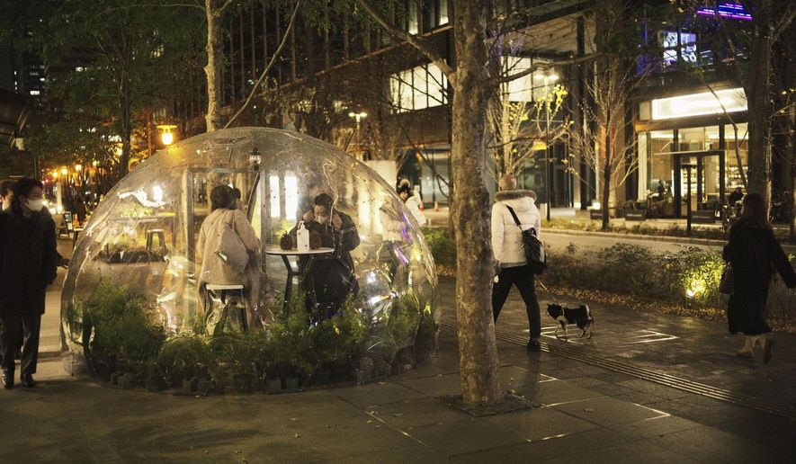 A man and a woman sit in a rest area with a clear dome installed on a shopping street in Tokyo, Thursday, Dec. 24, 2020. A bottle of disinfectant was also provided for the public to use. (AP Photo/Hiro Komae)