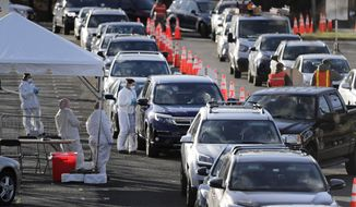 FILE - In this March 24, 2020, file photo, staff at a drive-thru COVID-19 testing site talk to people waiting in line in their cars at the PNC Bank Arts Center in Holmdel, N.J. (AP Photo/Seth Wenig, File)