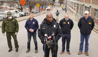 Nashville Police Chief John Drake, center, speaks during a news conference Friday, Dec. 25, 2020, in Nashville, Tenn. An explosion that shook the largely deserted streets of downtown Nashville early Christmas morning shattered windows, damaged buildings and wounded three people. Authorities said they believed the blast was intentional. (AP Photo/Mark Humphrey)