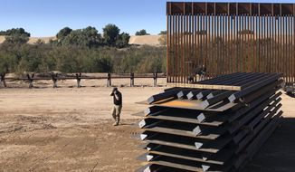 In this Jan. 10, 2020, photo, a man passes new border wall sections as they replace the old fencing near Yuma, Arizona. (AP Photo/Elliot Spagat) **FILE**