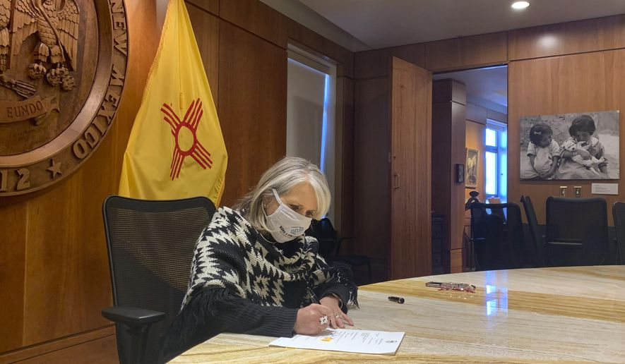 FILE - In this Nov. 25, 2020, file photo provided by the New Mexico Office of the Governor, Gov. Michelle Lujan Grisham signs a $330 million economic relief package aimed at helping small businesses and out-of-work New Mexicans while at the State Capitol in Santa Fe, N.M. From lockdowns in tribal communities to the economic and social fallout that has reverberated throughout New Mexico, the coronavirus pandemic dominated headlines in 2020. New Mexico had among the toughest public health restriction in the nation early on as Grisham called for the closure of gyms, salons and other businesses deemed nonessential. Public gatherings were banned, sports were cancelled, curbside became the norm, funerals were frowned upon and schools were forced to go virtual. (New Mexico Office of the Governor via AP, File)