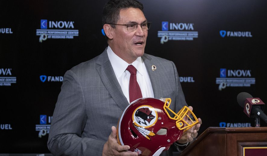 FILE - In this Jan. 2, 2020, file photo, Washington Redskins head coach Ron Rivera holds up a helmet during a news conference at the team's NFL football training facility in Ashburn, Va. Washington's NFL team finally joined the 21st century by dumping its racist nickname, though it took the greatest national awakening since the 1960s to finally draw out some semblance of shame from owner Dan Snyder. (AP Photo/Alex Brandon, File)