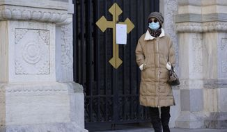 A visitor wearing a mask to protect from the coronavirus walks by a closure notice outside the Wangfujing Church in Beijing on Friday, Dec. 25, 2020. Official churches in the Chinese capital abruptly canceled Mass on Christmas Day in a last-minute move owing to the pandemic. (AP Photo/Ng Han Guan)