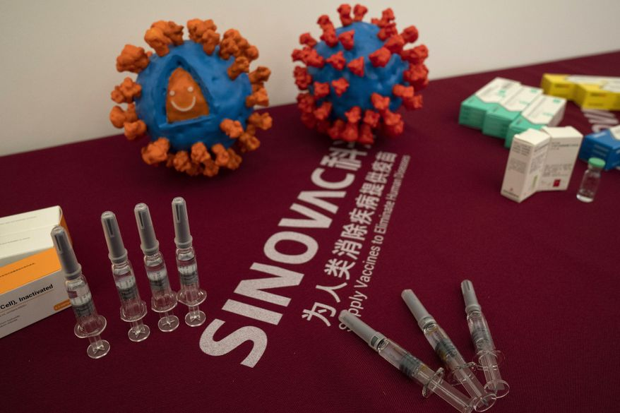 Syringes of a vaccine for COVID-19 and models depicting the coronavirus are displayed at the Sinovac factory in Beijing on Thursday, Sept. 24, 2020. With rich countries snapping up supplies of COVID-19 vaccines, some parts of the world may have to rely on Chinese-developed shots to conquer the outbreak. The question: Will they work? (AP Photo/Ng Han Guan) ** FILE **