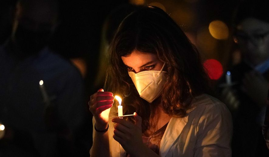 A woman wears a protective face mask while holding a candle during an outdoor Christmas Eve Service of Lights at the Granada Presbyterian Church, Thursday, Dec. 24, 2020, in Coral Gables, Fla. The service was held outdoors for safety reasons to protect against the spread of the coronavirus. (AP Photo/Lynne Sladky)