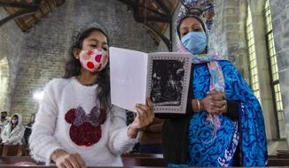 Indian Christians, who are registered members of St. John in the Wilderness church, attend the Christmas mass in Dharmsala, India, Friday, Dec. 25, 2020. The church which was built in 1852, is currently closed to general visitors due to COVID-19 restrictions. (AP Photo/Ashwini Bhatia)