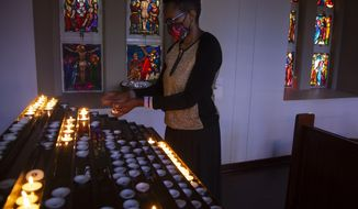 A worshipper wearing a face mask stands in front of lit candles prior to a morning Christmas Mass at the Rosebank Catholic Church in Johannesburg, Friday, Dec. 25, 2020. (AP Photo/Denis Farrell)