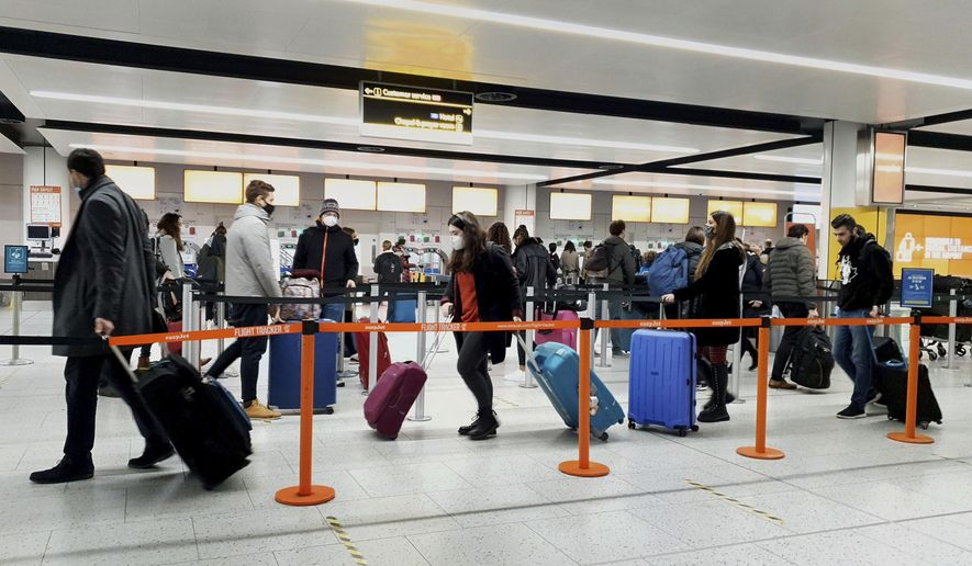 In this Dec. 20, 2020, file photo, passengers queue for check-in at Gatwick Airport in West Sussex, England, south of London. The United States will require airline passengers from Britain to get a negative COVID-19 test before their flight, the Centers for Disease Control and Prevention announced late Thursday, Dec. 24. The U.S. is the latest country to announce new travel restrictions because of a new variant of the coronavirus that is spreading in Britain. (Gareth Fuller/PA via AP)