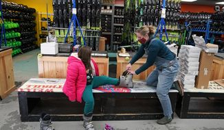 Meredith Hopkins, right, helps fit ski boots on Makenna Houghton at the ski shop at McIntyre Ski Area, Wednesday, Dec. 16, 2020, in Manchester, N.H. Over the summer, people looking to get out of the house snapped up boats, bicycles and patio furniture, figuring they were safer socializing and being active outdoors than inside. Now that temperatures are dropping, they're buying snowshoes, skis, boots and winter coats, boosting the beleaguered retail sector. (AP Photo/Charles Krupa)