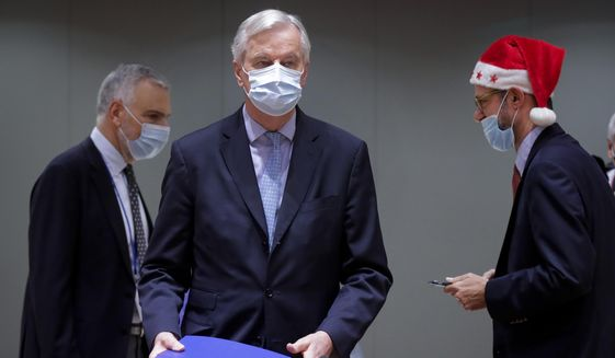 In this Friday, Dec. 25, 2020, file photo, a colleague wears a Christmas hat as European Union chief negotiator Michel Barnier, center, carries a binder of the Brexit trade deal during a special meeting of Coreper, at the European Council building in Brussels. The European Union and the United Kingdom made public Saturday the vast agreement that is likely to govern future trade and cooperation between them from Jan. 1, setting the 27-nation bloc's relations with its former member country and neighbor on a new but far more distant footing. (Olivier Hoslet, Pool via AP, File)