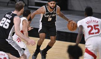 San Antonio Spurs' Patty Mills (8) looks to get past Toronto Raptors' Chris Boucher (25) during the first half of an NBA basketball game Saturday, Dec. 26, 2020, in San Antonio. (AP Photo/Darren Abate)