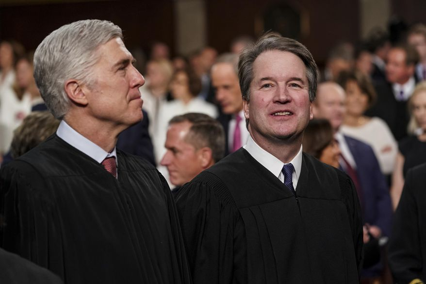In this Feb. 5, 2019 file photo, Supreme Court Associate Justices Neil Gorsuch, left, and Brett Kavanaugh watch as President Donald Trump arrives to give his State of the Union address to a joint session on Congress at the Capitol in Washington. (Doug Mills/The New York Times via AP, Pool, File)