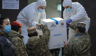 Men wearing full protective suits against coronavirus, take a box containing COVID-19 vaccines, from military personnel at the National Center for Storage of the COVID-19 Vaccine, a military run facility, in Bucharest, Romania, Saturday, Dec. 26, 2020. Romanian authorities will start COVID-19 vaccinations on Dec. 27, 2020. (AP Photo/Vadim Ghirda)