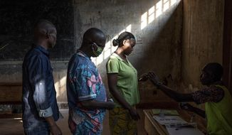 People cast their votes for presidential and legislative elections, at the Lycee Boganda polling station in the capital Bangui, Central African Republic Sunday, Dec. 27, 2020. President Faustin-Archange Touadera and his party said the vote will go ahead after government forces clashed with rebels in recent days and some opposition candidates pulled out of the race amid growing insecurity. (AP Photo)