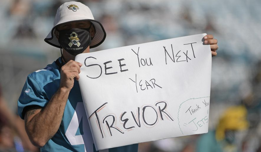 A Jacksonville Jaguars fan hold up a sign hoping that Clemson quarterback Trevor Lawerence will be the first pick for the Jacksonville Jaguars during the second half of an NFL football game against the Chicago Bears, Sunday, Dec. 27, 2020, in Jacksonville, Fla. (AP Photo/Phelan M. Ebenhack)