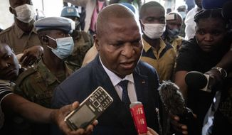 President Faustin-Archange Touadera speaks to the media after casting his vote at the Lycee Boganda polling station in the capital Bangui, Central African Republic, Sunday, Dec. 27, 2020. Touadera and his party said the vote will go ahead after government forces clashed with rebels in recent days and some opposition candidates pulled out of the race amid growing insecurity. (AP Photo)
