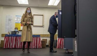 U.S. Sen. Kelly Loeffler, R-Ga., prepares to cast her ballot alongside her husband, Jeff Sprecher, right, during early voting in runoff elections at Chastain Park Gymnasium in Atlanta's Chastain Park neighborhood, Wednesday, Dec. 16, 2020. (Alyssa Pointer/Atlanta Journal-Constitution via AP)  **FILE**