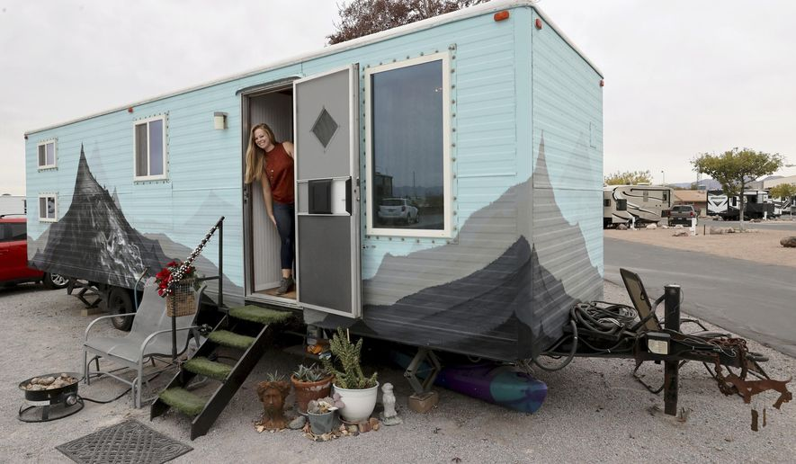 Hannah Doss poses for a photo at her tiny home in Boulder City, Nev., Friday, Dec. 11, 2020. Doss bought the old railroad trailer that she and her parents converted into a tiny house. (K.M. Cannon/Las Vegas Review-Journal via AP)